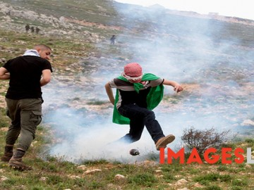 Palestinian demonstrators react amidst tear gas smoke fire by Israel forces during a protest to mark land day in village of Madama, south of Nablus, on March 30, 2017 in the Israeli occupied West Bank. Land Day marks the killing of six Arab Israelis during 1976 demonstrations against Israeli confiscations of Arab land.